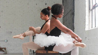 Two woman in tutus sitting on a bench and lacing up ballet shoes