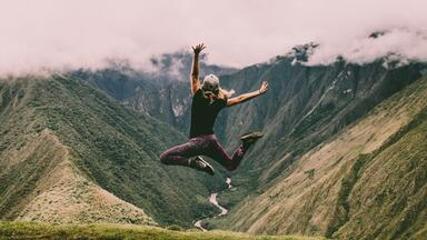 Woman jumping for joy in front of clouds and mountains