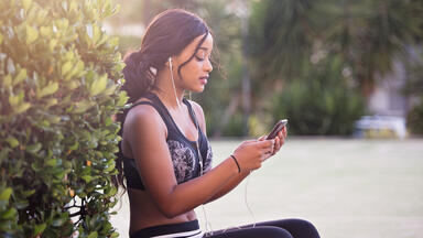 woman listening to music on phone outside