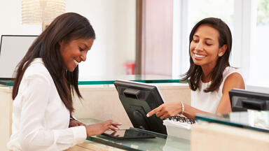 woman helping woman sign in on tablet