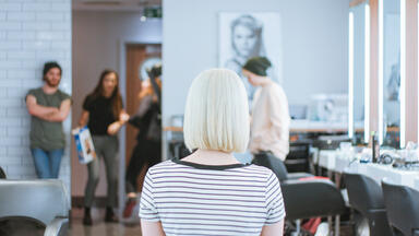 woman with platinum hair sitting in a salon