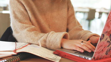 woman in tan sweater with a pink floral laptop