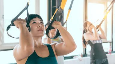 Woman performing bicep curl on a TRX suspension trainer