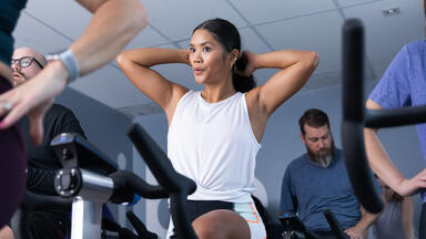 woman in an indoor cycling class working out with group