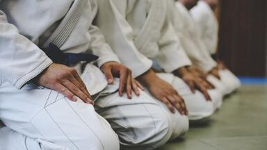 Martial arts students sitting on the floor in a line