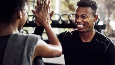 Two smiling clients high five at the gym
