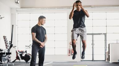 Sports trainer with jumping athlete