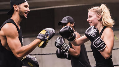 A woman boxing with a coach at Tribute Boxing