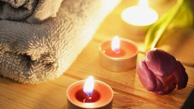 Candles and rose by folded towels