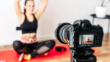 Fitness instructor filming a workout video in front of a camera on a tripod