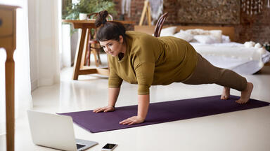 Woman doing a livestream yoga class on a mat in her home next to her computer
