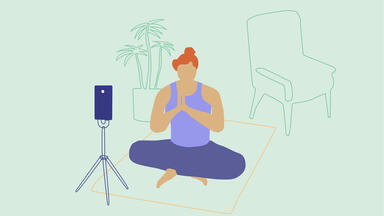 Woman live streaming a yoga class in front of a phone on a tripod