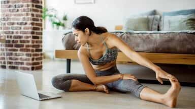Woman stretching in workout clothes in front of a computer