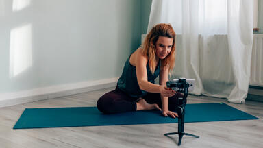 Fitness instructor at home on a mat and setting up virtual class with a phone on a tripod