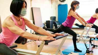 three women in masks on pilates reformers