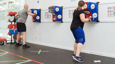 A man and a woman using a punching bag at HighLow Fitness