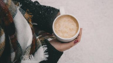 woman in winter coat and scarf holding coffee