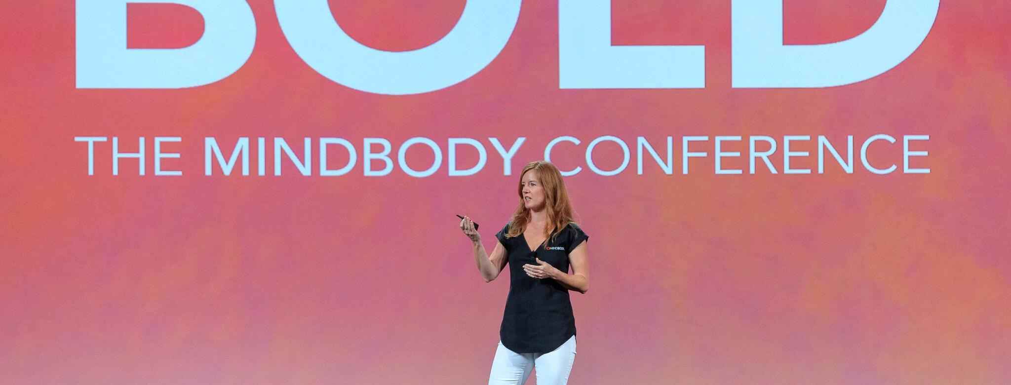 Presenter discussing wellness industry trends at BOLD