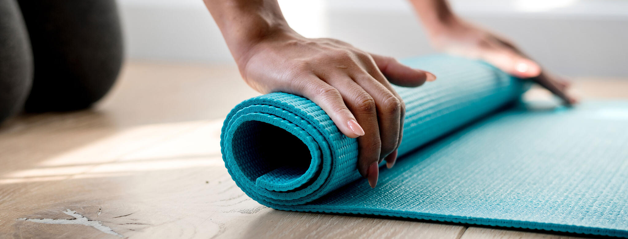 Woman rolling out a yoga mat