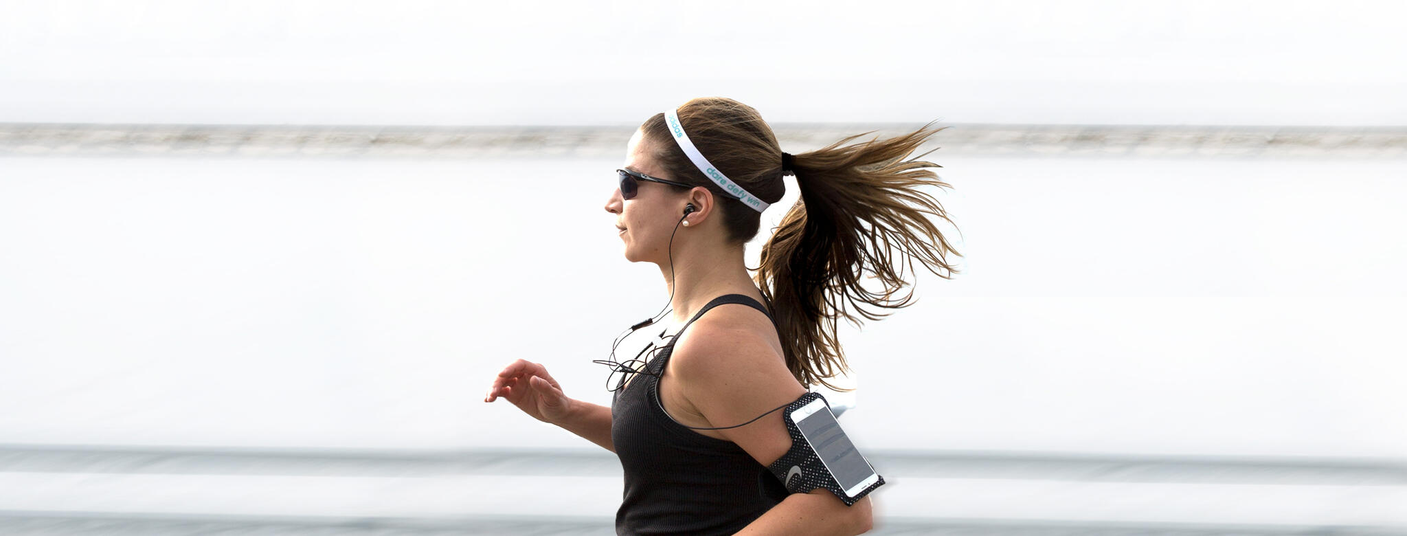 Woman running in sunglasses wearing a fitness tracker