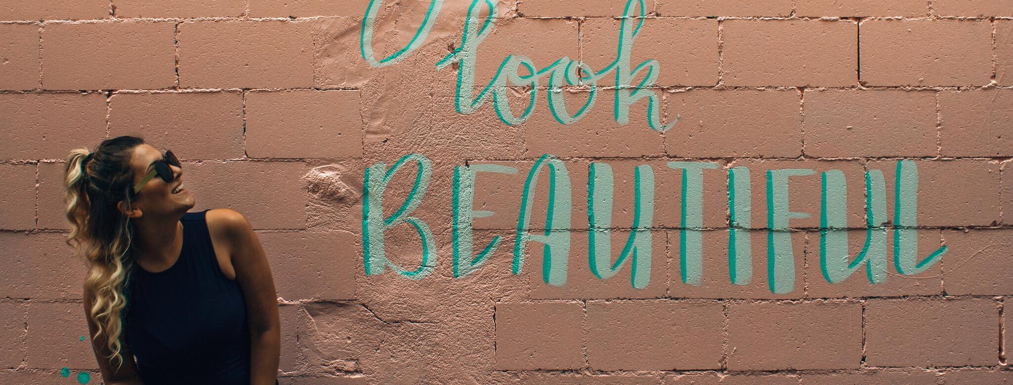 "Woman leaning on a painted brick wall with a ""You look beautiful"" mural"