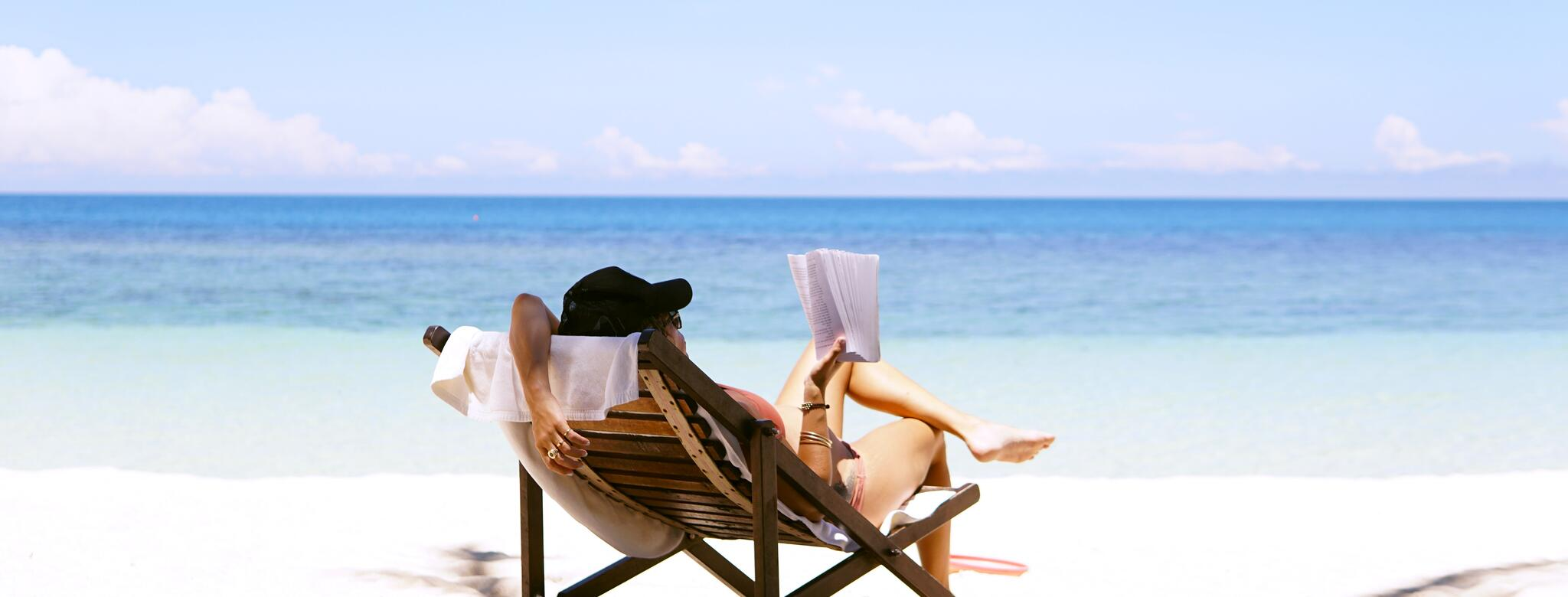 Woman reading a book on the beach in a chair