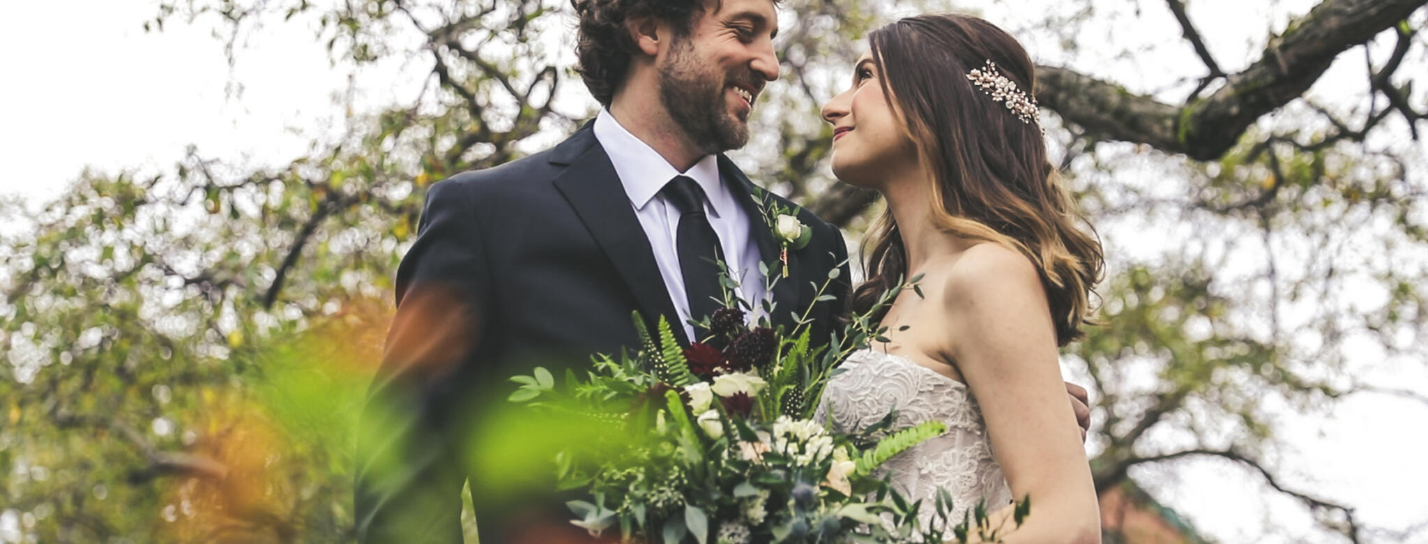groom and bride outside with bouquet of flowers