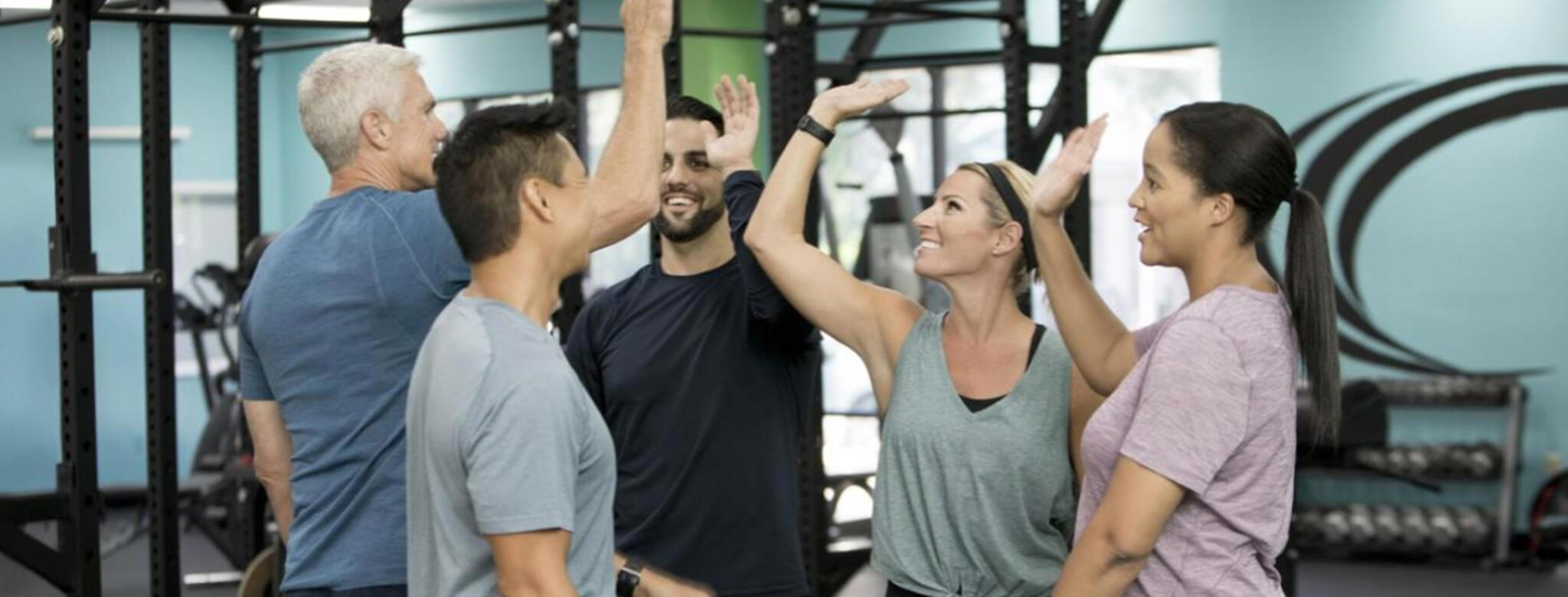 group of people high fiving in the gym