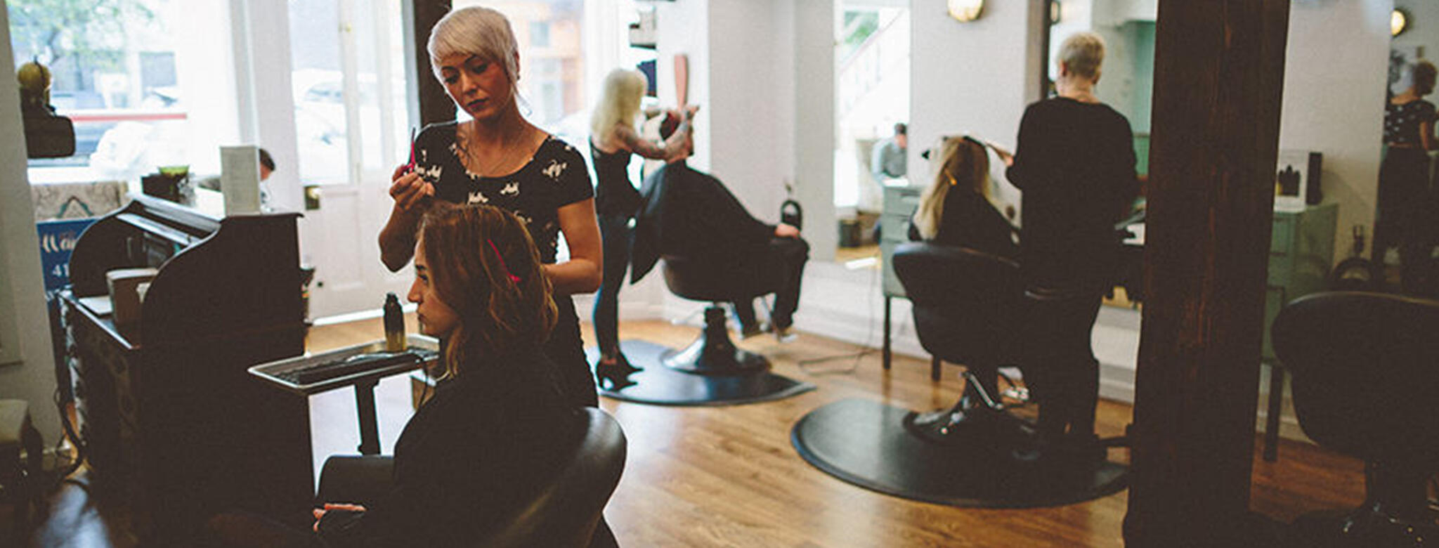 woman getting hair done by stylist in salon