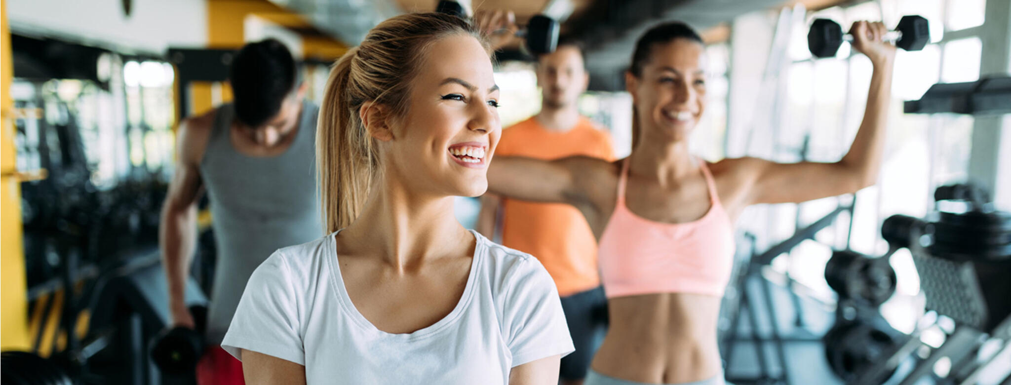 blonde woman lifting weights with others in gym
