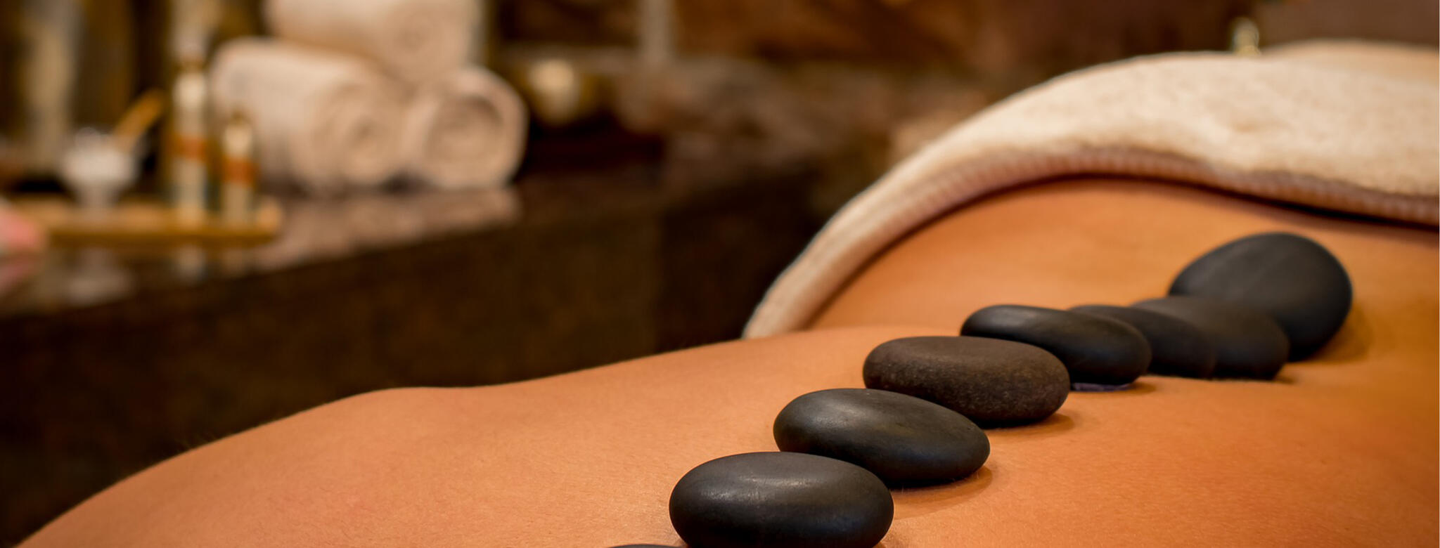 hot stones placed on persons back in spa