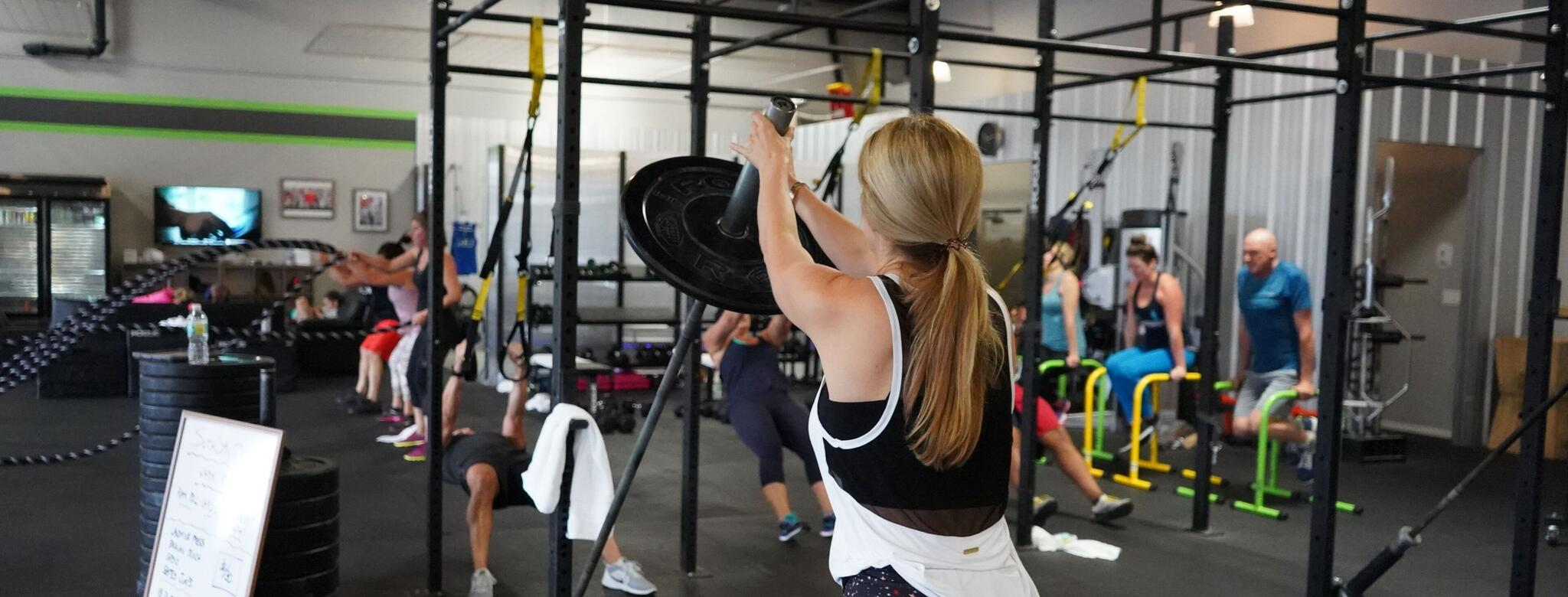 Woman exercising with heavy weights  in a high-intensity fitness studio
