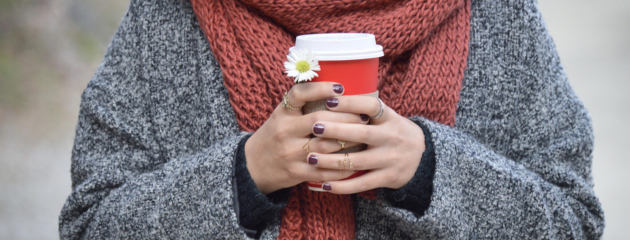 woman in scarf holding red and white coffee cup with manicured hands