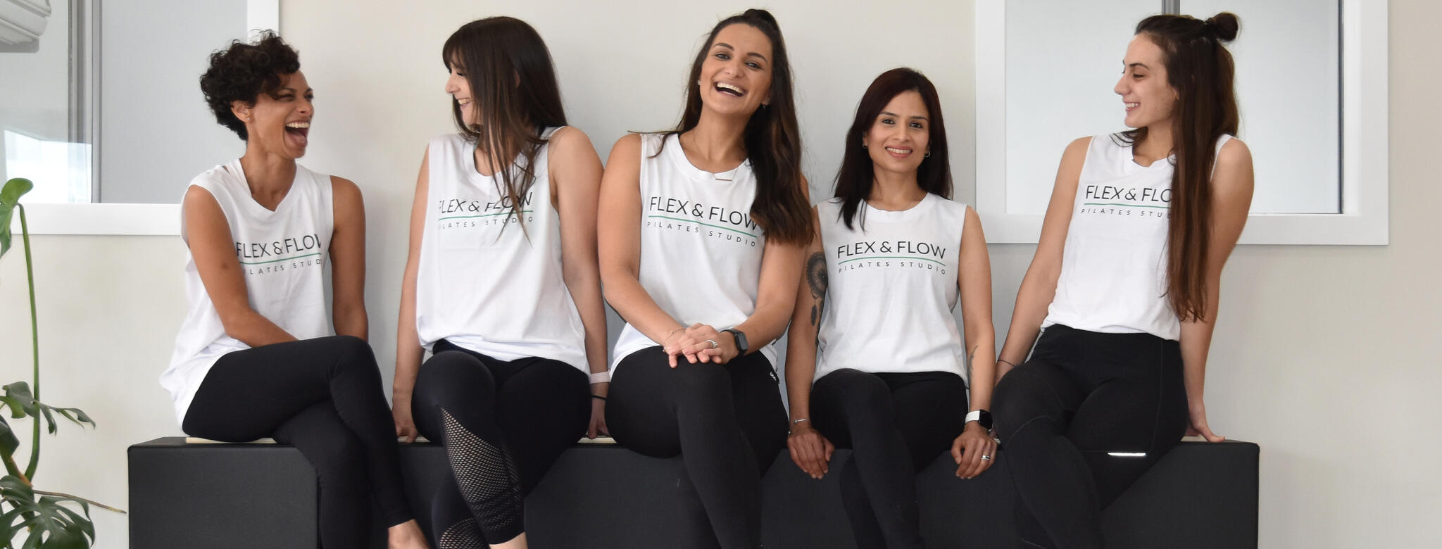 The staff of Flex and Flow Pilates joking together in the exercise room