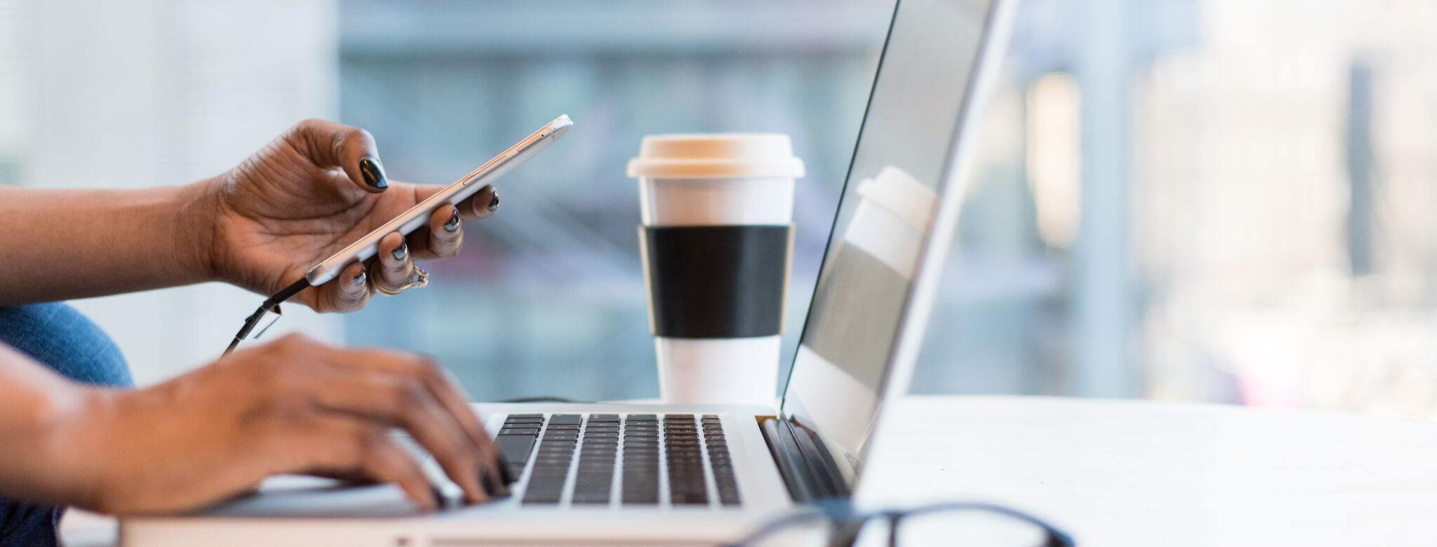 woman on laptop and smartphone with coffee cup and glasses