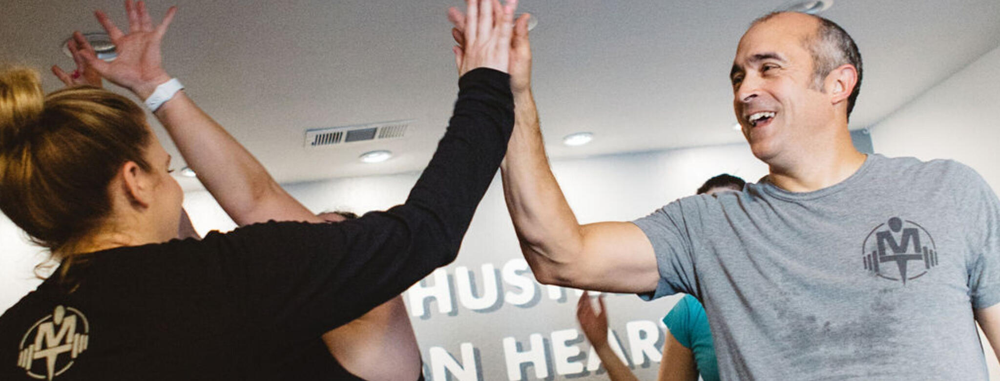 man and woman giving high five in gym