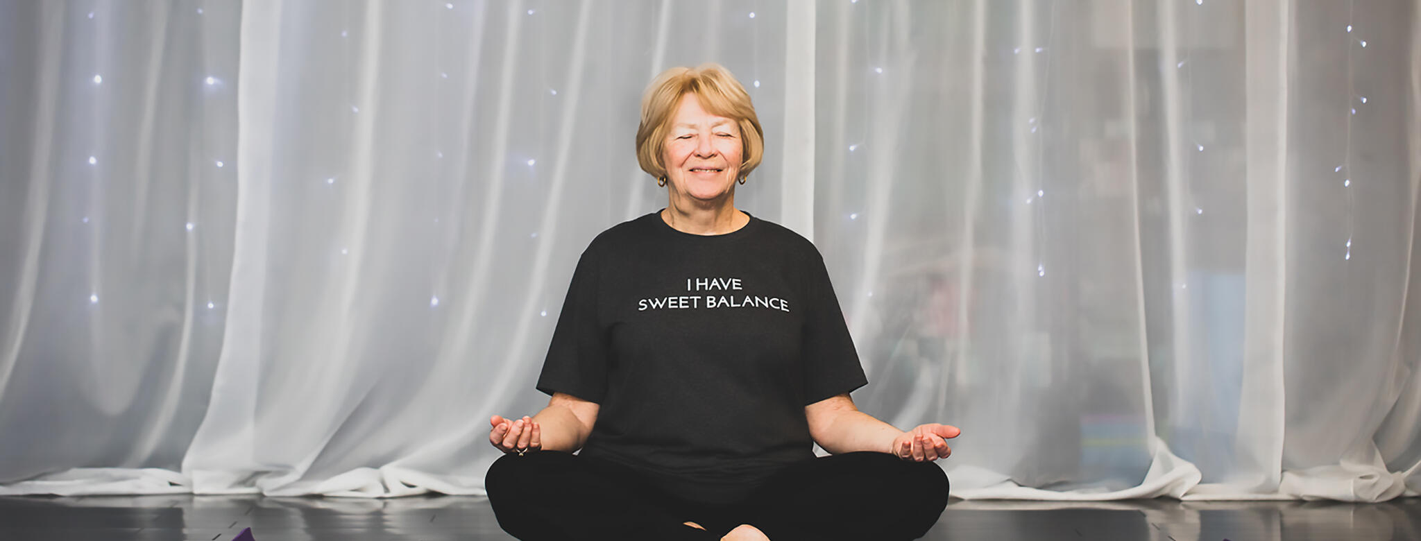An older woman practicing yoga at Sweet Balance