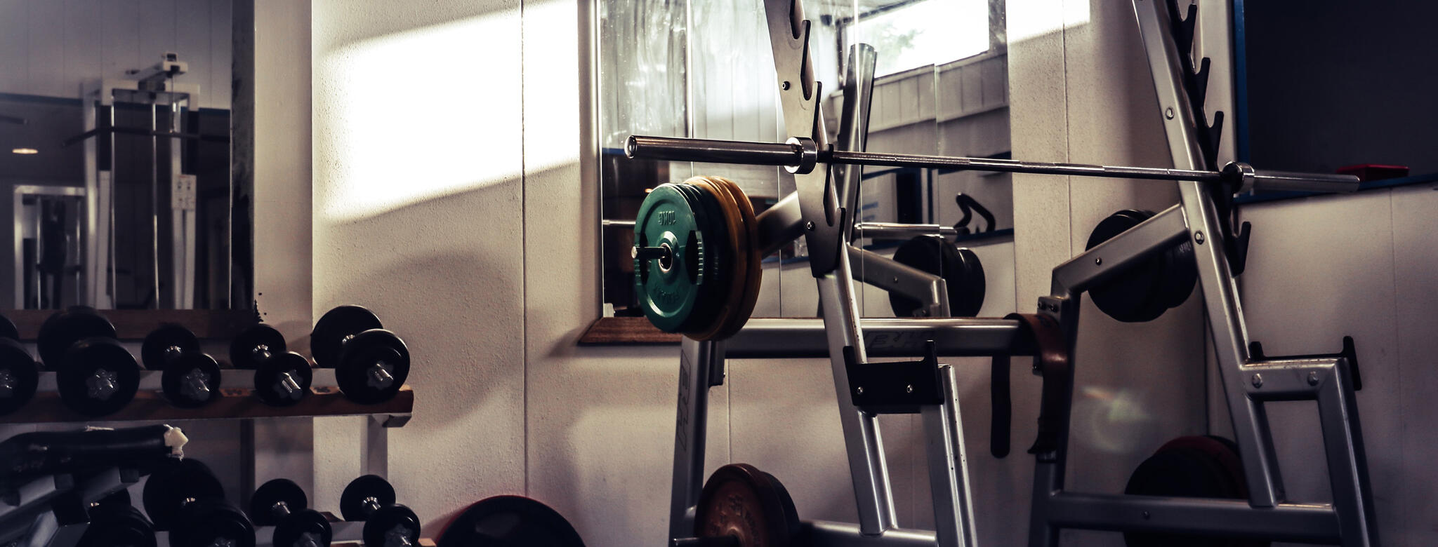Abandoned weights in a dark, empty gym