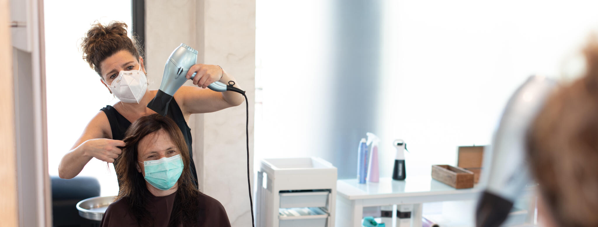Hair stylist wearing a mask while blow drying hair