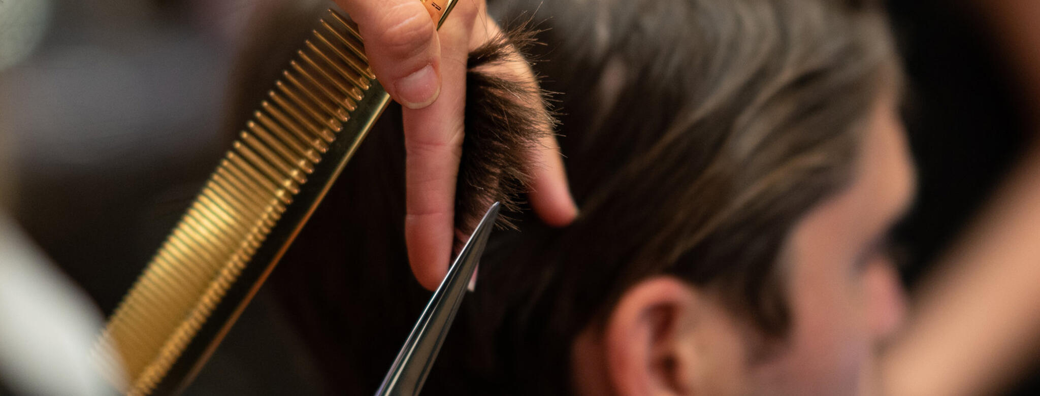 Stylist cutting hair at Emerson Joseph