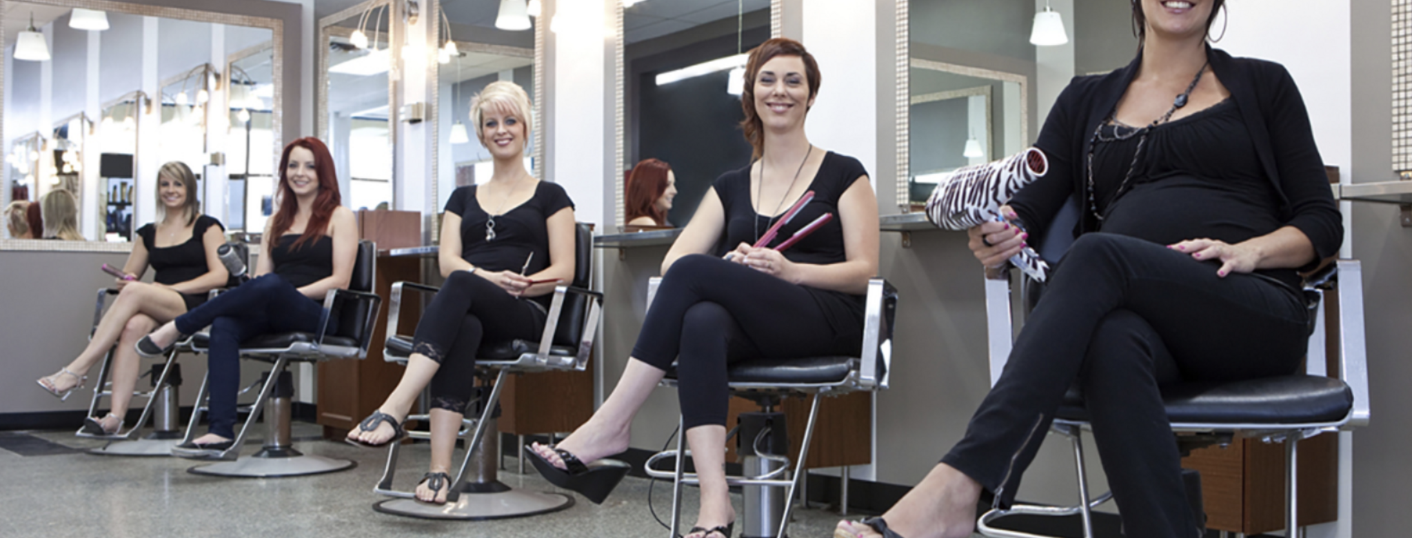 hair stylists sitting in chairs in salon