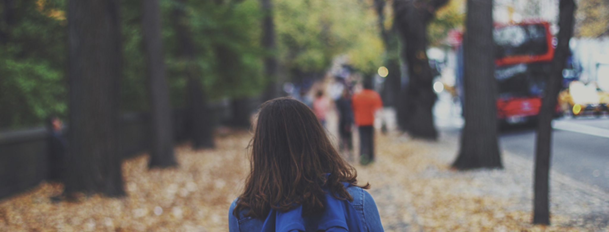 girl with backpack on walking down street in fall