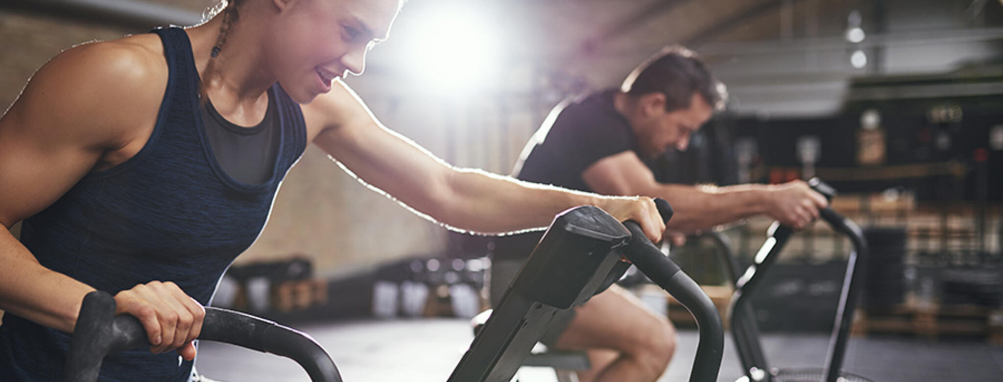 Woman working hard on stationary bike, man biking in background after purchasing introductory offers