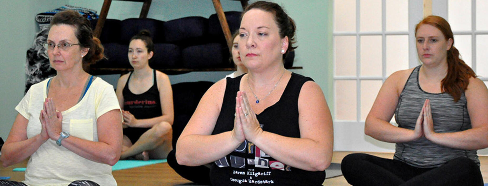 Murderinos practicing yoga at charity event for End the Backlog