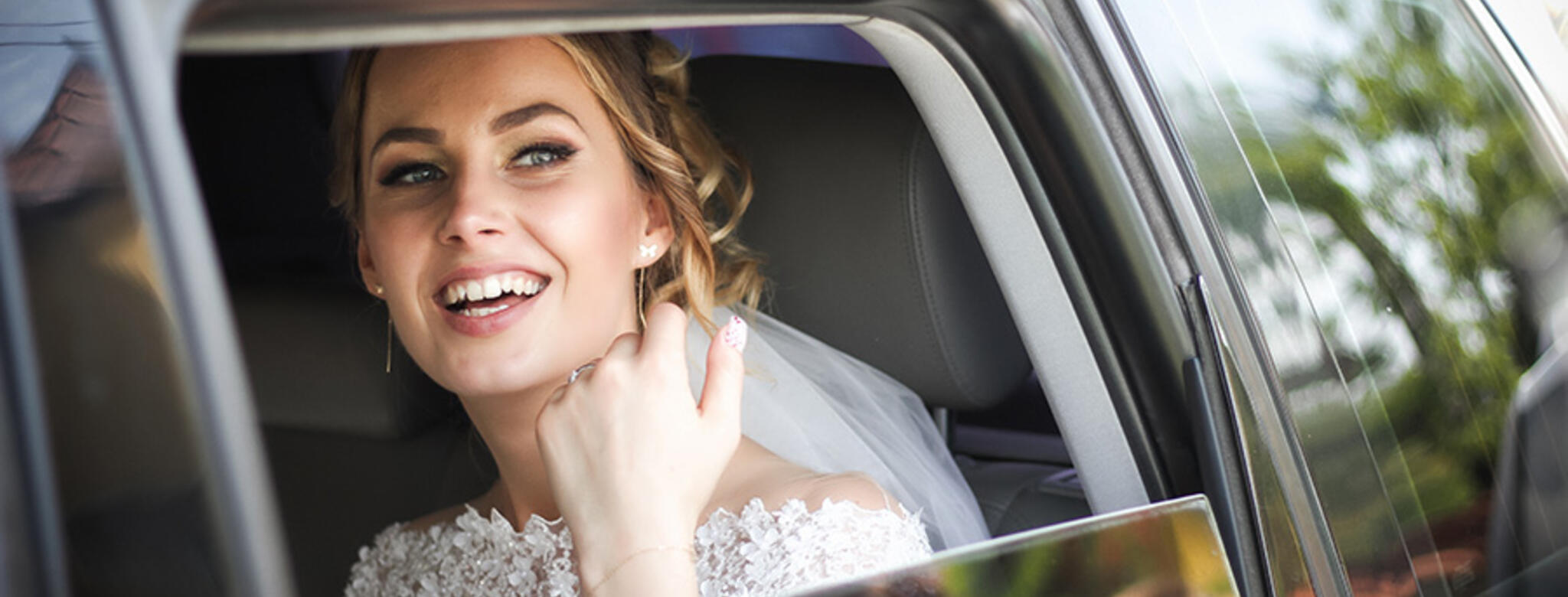 Bride smiling in car window
