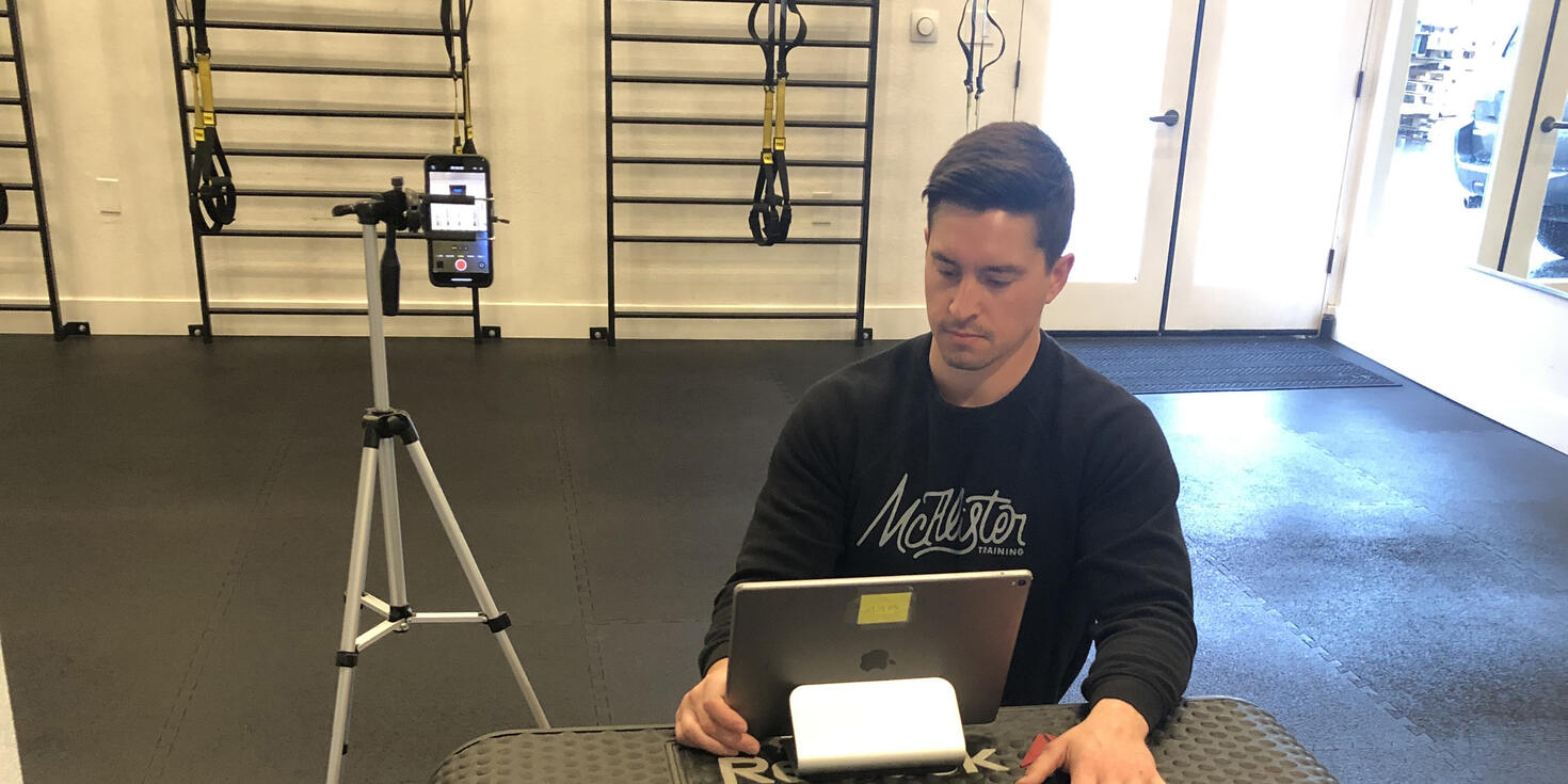 Fitness instructor sits next to live streaming recording setup