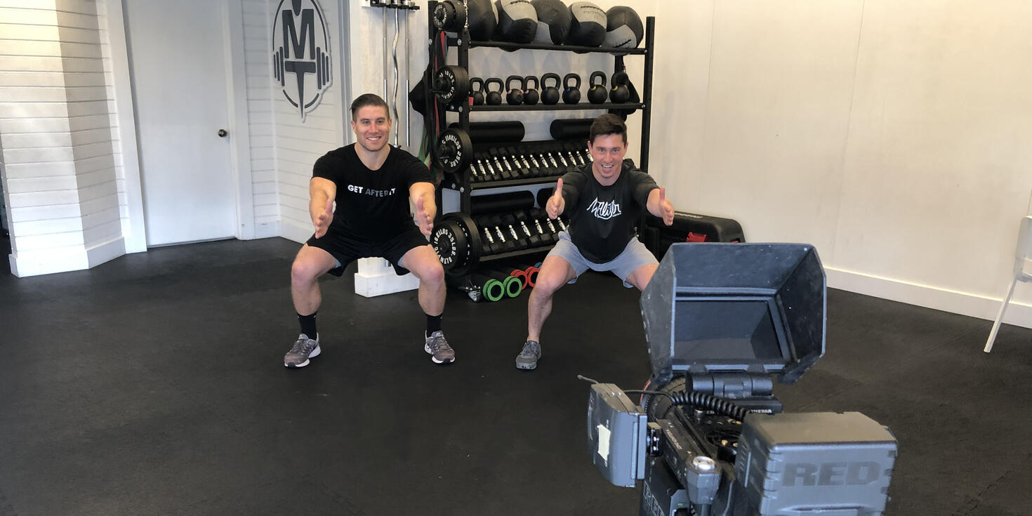 Two fitness instructors film a squats workout with a video camera