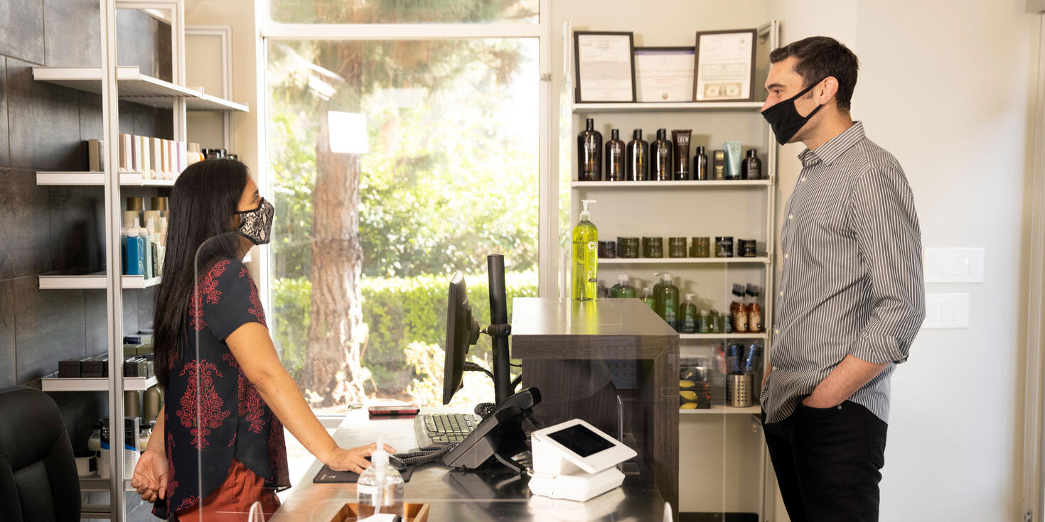 salon stylists helping male client at checkout