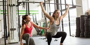 Fitness instructor helps client with overhead squat form