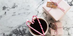 Coffee mug with candy canes on top and holiday gifts to the right